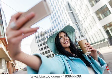 Brunette in hat takes pictures of herself on street