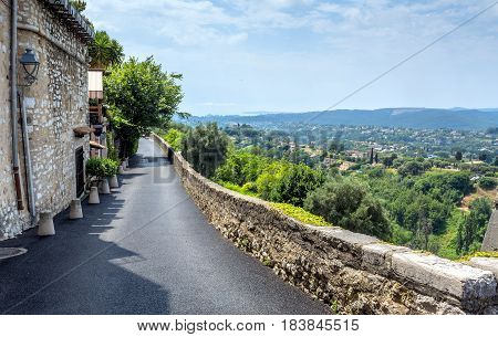 Saint Paul de Vence, France - June 30, 2016: day view of typical street with panoramic view in Saint Paul de Vence France. It is popular destination for a large number of artists poets and writers.