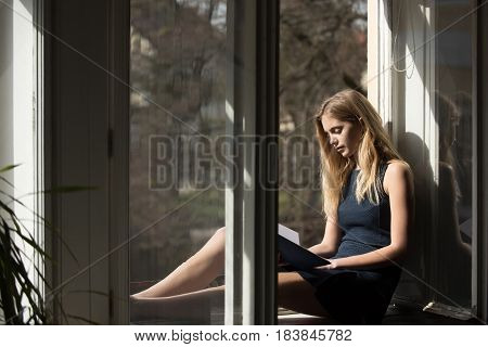 Leisure and relaxing Pretty girl or young woman student teenager with cute young face and blond long hair in summer dress reading book at open window on sill on urban background