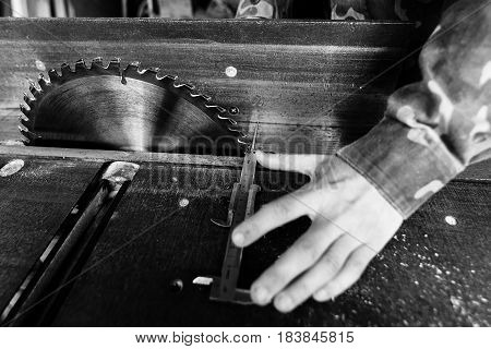 Circular saw.. Carpenter measures the width of the board with a calipers in the workplace. Carpenter tool