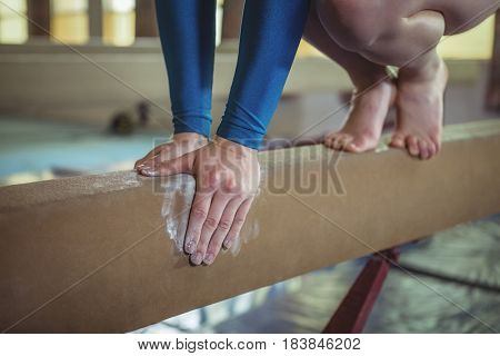 Close-up of female gymnast practicing gymnastics on the balance beam