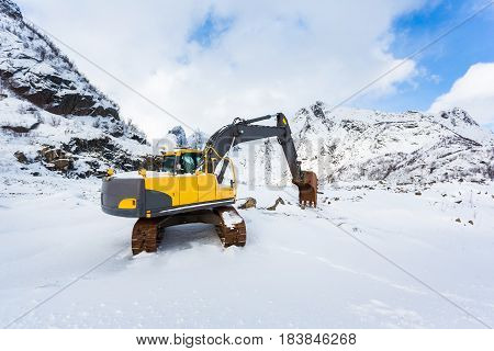 Excavator in the snowy mountains of Lofotens Norway