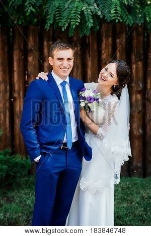 Bride embraces the groom. The bride and groom near the wooden wall from logs in the park. Wedding couple in love at wedding day