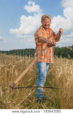 Modern farmer with scythe at ripe wheat field