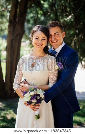 Bride and groom hugs in the park. Groom embraces the bride. Wedding couple in love at wedding day