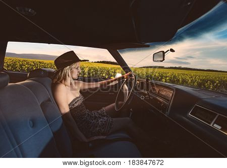 Young female driver on open road. Woman driving vintage car on road trip.