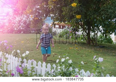 Cute baby boy little child with long blond hair ponytail in blue striped clothes walking barefoot on green grass in park on sunny summer outdoors on natural background. childhood and happiness