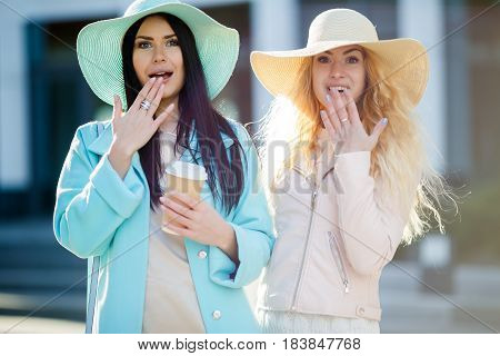 Two young women on blurred building background