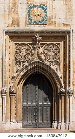 West entrance door of Church of Saint Mary the Great with Cambridge University clock above. Cambridge United Kingdom