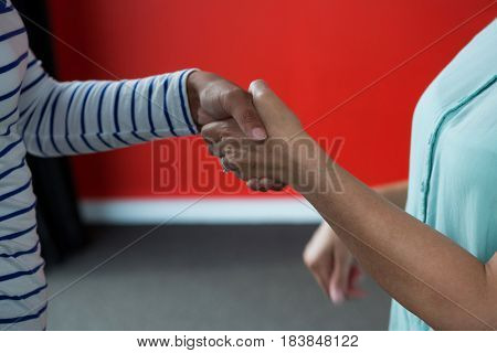 Close-up of women shaking hands with each other in office