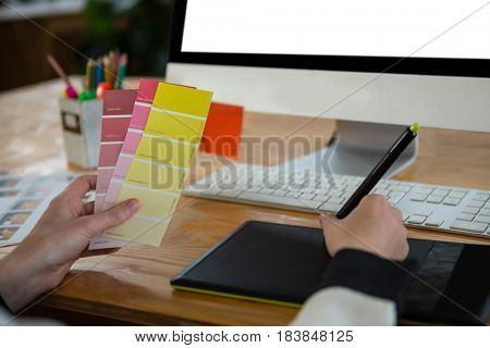Close-up of a female graphic designer working at desk in creative office