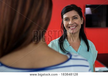 Happy woman interactive with colleague in office