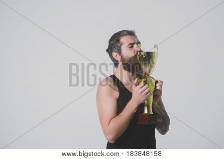 Bearded Happy Man Kissing Gold Champion Cup On Grey Background