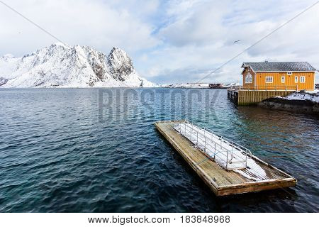 Wooden floating pier in the sea against the background of snowy Lofoten mountains