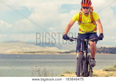 Mountain biker riding on bike at the sea and summer mountains. Man rider cycling MTB on country road or single track. Sport fitness motivation inspiration in beautiful inspirational landscape.