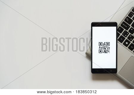 Bratislava, Slovakia, April 28, 2017: QR code on smartphone screen placed on laptop keyboard. Empty place to write information.