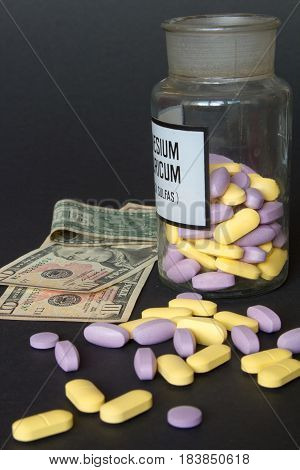 the medical pills are on a money. Colorful pills and money on a black background.