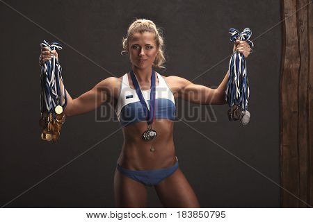 Strong Athletic Woman Fitness Model Showing Her Medals. Young Sexy Bodybuilder Winner With Perfect B