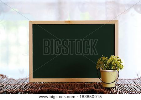 Green flower pot with green board wooden decoration on blur window background