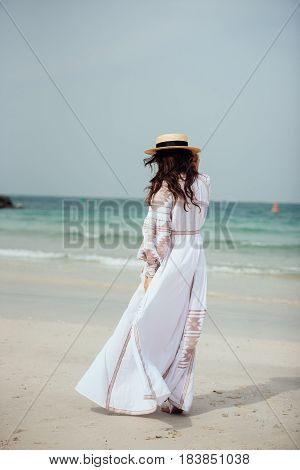 Beautiful young woman in long white dress with long hair and hat goes along the beach