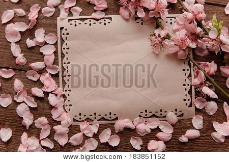 Note postcard writing retro peach blossoms on a wooden vintage tablee peach flower on the table background. Spring pink flowers.