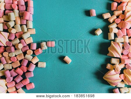Marshmallows Background or texture of colorful mini marshmallows Blue textured background with multicolored marshmallows on the sides