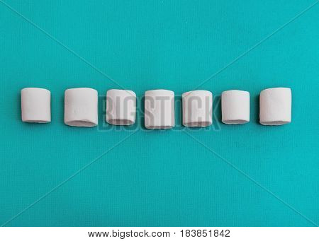 Marshmallows Background or texture of colorful mini marshmallows Seven white marshmallows are lying on a blue background