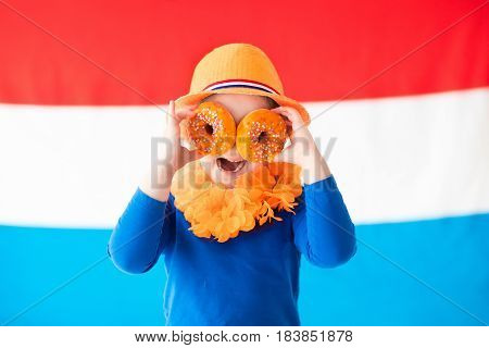 Little Dutch boy girl wearing country symbols eating orange donuts celebrating King day. Children support Holland sport team. Kids from the Netherlands. Young sport fans with national flag.