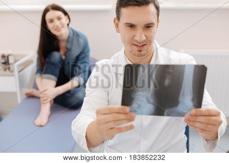 Good news. Delighted positive nice doctor looking at the X ray image and smiling while having good news for his patient