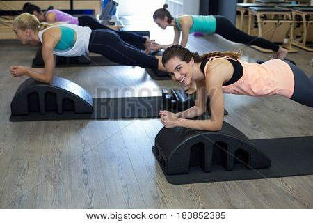 Group of women exercising on arc barrel in gym