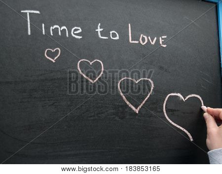 The inscription of the time to love is written by the hand of the girl chalk on a slate background and paints the hearts