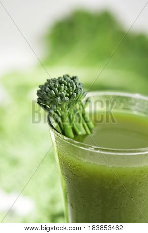 a green smoothie served in a glass topped with a stem of broccolini and some leaves of cabbage and kale in the background