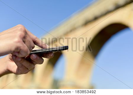 closeup of a young caucasian man using a smartphone outdoors in front of some ancient architectural remains