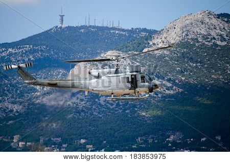 Helicopter bell uh 1,Exhaust gases machine gunner mountain background.