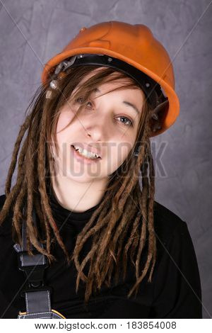 girl in safety helmet orange vest holding hammer tool. Attractive woman working as construction worker.