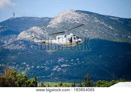 Helicopter bell uh 1,mountain background antennas exhaust smoke