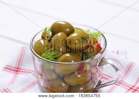 cup of marinated green olives on checkered dishtowel - close up
