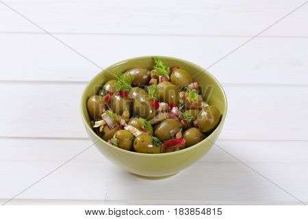 bowl of marinated green olives on white wooden background