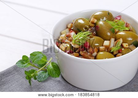 bowl of marinated green olives on grey place mat - close up
