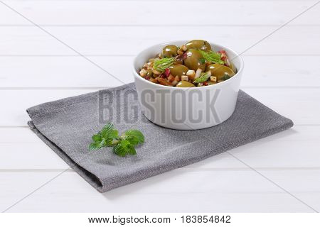 bowl of marinated green olives on grey place mat