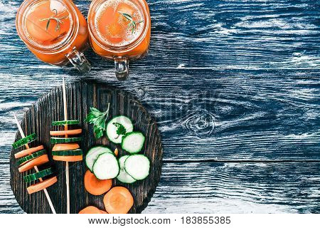 Carrot smoothie in two mason jars on black wood background with slices of fresh carrot and cucumber. Top view