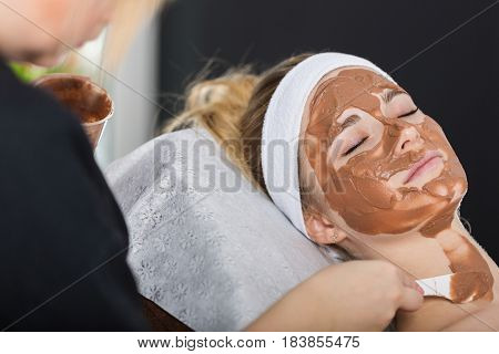 Woman Getting Chocolate Mask Treatment In Spa