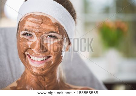 Young Woman During Refreshing Chocolate Mask Treatment In Spa