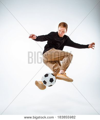 A portrait of a fan with ball on gray studio background. Freestile concept