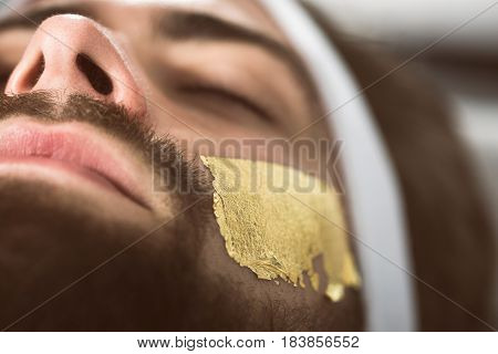 Close-up gold mask leaf at man's face