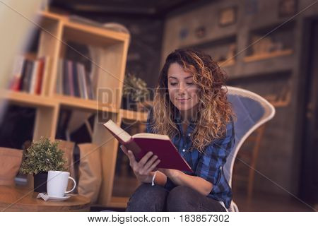 Beautiful young woman sitting in a cafe enjoying her morning coffee and reading a book
