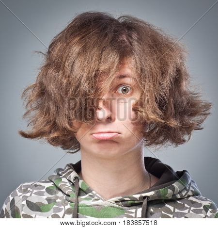 portrait of a girl with disheveled hair, surprise, emotions cool in Studio on gray background