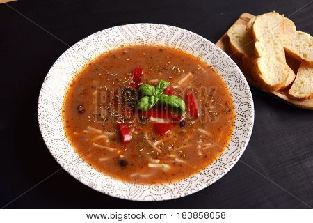 Homemade soup with  beans and vegetables  on a black wooden background.