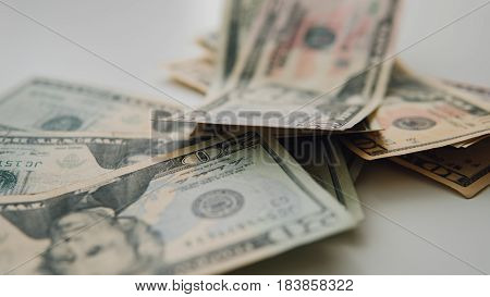 Close-up The Dollars Scattered On A White Background. Ten,five,twenty,fifty And One Hundred Dollars