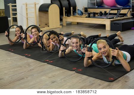 Group of fit women exercising with pilates ring in gym